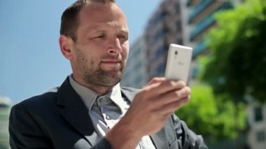 Businessman with smartphone in the city — Vídeo de stock