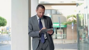 Businessman working on tablet in city — Stock video
