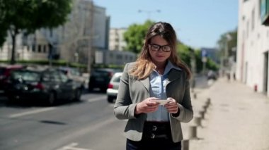 Businesswoman with smartphone in city — Stockvideo