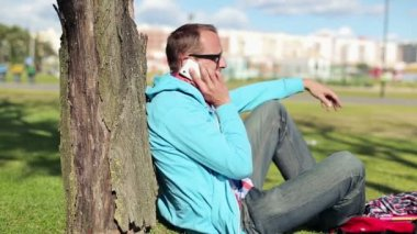 Student talking on cellphone in park — Wideo stockowe