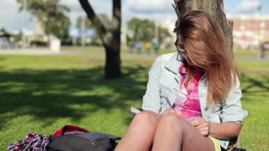 Female student studying in park — Stock Video
