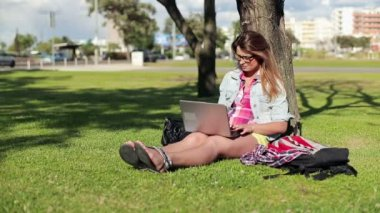 Female student with laptop in park — Video Stock