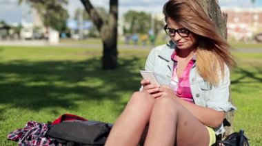 Pretty female student texting in park — Wideo stockowe