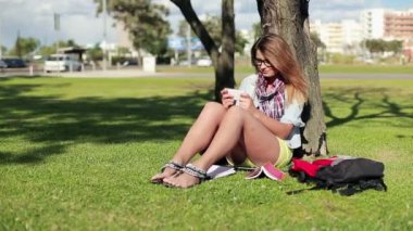 Pretty female student texting in park — Video Stock