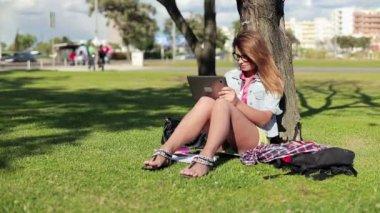 студентка с планшетом в парке — Стоковое видео