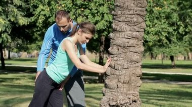 Woman stretching and bending by tree — Stok video