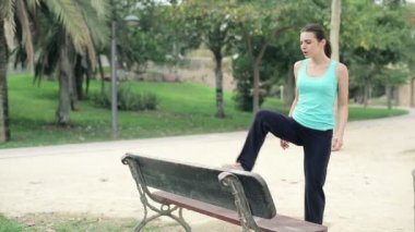 Jogger stretching legs by bench — Stok video