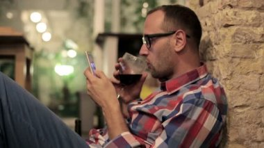 Man drinking wine and texting on smartphone — Stock Video