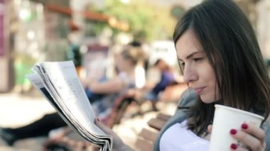 Businesswoman drinking coffee and reading newspaper — Stock Video