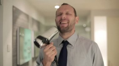 Businessman singing to blow-dryer — Stock Video
