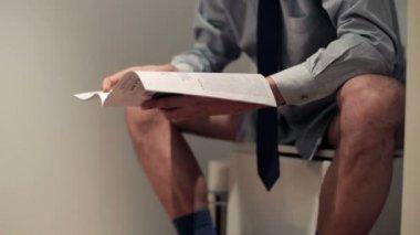 Businessman reading magazine on toilet — Stock Video