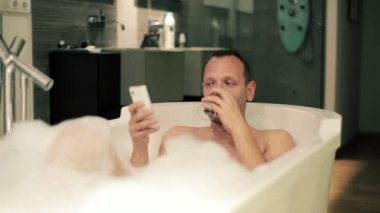 Man using smartphone in bathtub — Vídeo de Stock