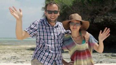 Couple waving hands to camera on beautiful beach — Stock Video