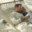 Couple with smartphone sitting on hammock on exotic beach — Stock Video #45217907