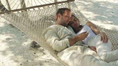 Met smartphone zittend op de hangmat op exotische beach (echt) paar — Stockvideo