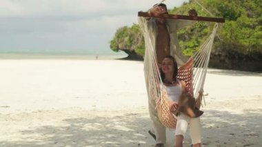 Couple in love talking, relaxing on hammock on tropical beach — Stock Video
