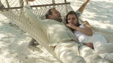 Couple lying on hammock waking up from nap, luxury resort — Stock Video