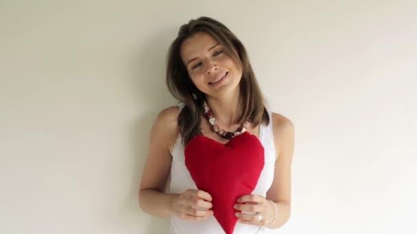 Mujer con almohada de corazón — Vídeo de stock