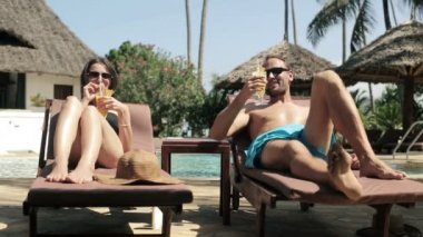 Couple drinking cocktails by  pool — Stock Video