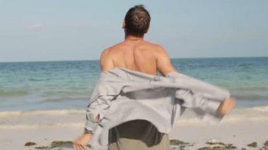 Man undressing on beach — Stock Video