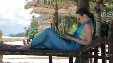 Woman with laptop on sunbed — Stock Video