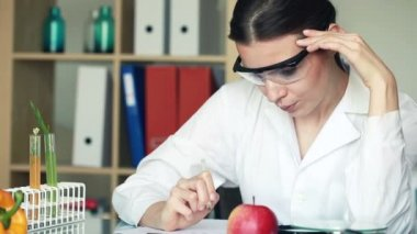 Female biochemist examine apple — Stock Video