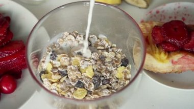 Pouring milk into bowl with muesli — Stock Video