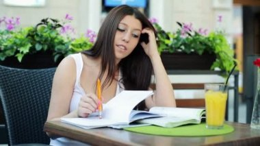 Student overwhelmed by her homework in cafe — Vídeo de stock