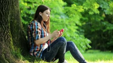 Woman listen to music in park — ストックビデオ