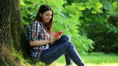 Woman texting sms in the park — Stockvideo