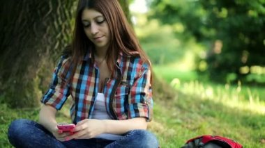 Student texting sms in the park — Stockvideo