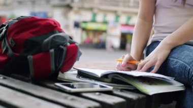 Student doing homework in notebook in the city — Stock Video