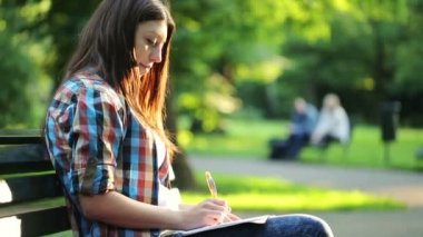 Student doing homework in the park — ストックビデオ