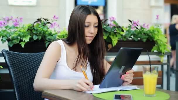 Estudiante haciendo los deberes con ayuda de la tableta — Vídeo de stock