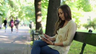 Женщина texting на смартфоне в парке — Стоковое видео
