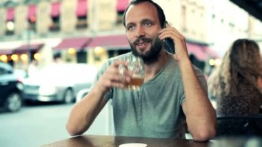 Man talking on cellphone and drinking beer — Stock Video
