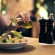 Woman pouring olive oil on salad — Stock Video #49792657