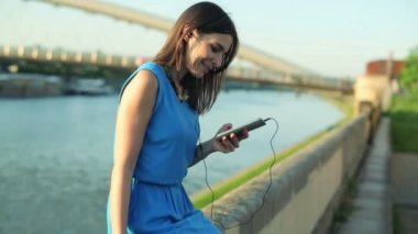 Woman listening music on smartphone by river — Stock Video