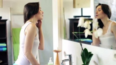 Woman checking her face in the mirror — Vidéo