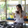 Woman chatting on cellphone in kitchen — Stock Video