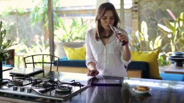 Woman watching photos on tablet in kitchen — Stock Video