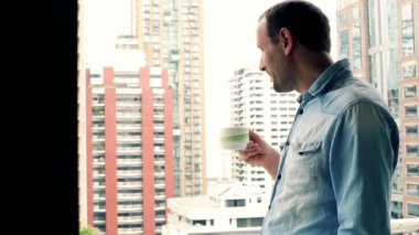 Man drinking coffee on balcony — Stock Video