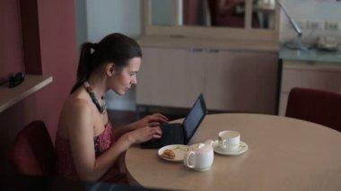 Mulher que trabalha no portátil pela tabela — Vídeo Stock