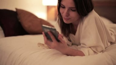 Woman with smartphone lying on bed — ストックビデオ