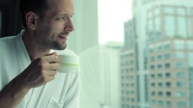 Man in bathrobe drinking coffee — Stockvideo