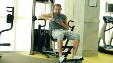 Man with smartphone in the gym — Stockvideo