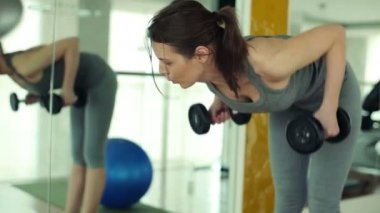 Woman exercising with dumbbells in the gym — Stock video