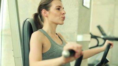 Woman exercising on rowing machine — Stockvideo