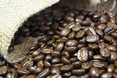 Granos de café fuera de su bolsa de yute — Foto de Stock