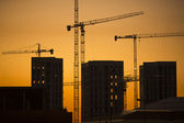 Cranes at sunset. Industrial construction cranes and building silhouettes over sun at sunrise. — Foto Stock